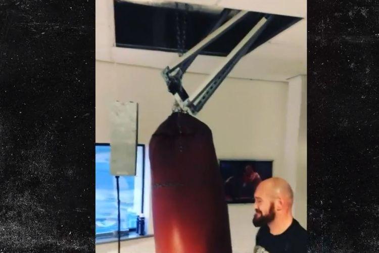 Tyson Fury memeriksa samsak yang ia pukuli. Pukulan-pukulan Fury membuat samsak itu lepas dan atap di sasasana Morecambe Bay rubuh pada Selasa (17/11/2020).