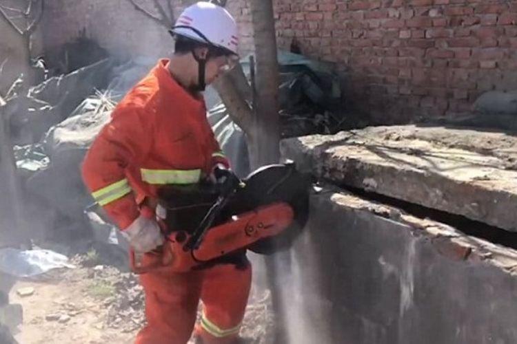Seorang petugas pemadam kebakaran menggunakan gergaji mesin membongkar penutup septik tank untuk menyelamatkan seorang bayi.