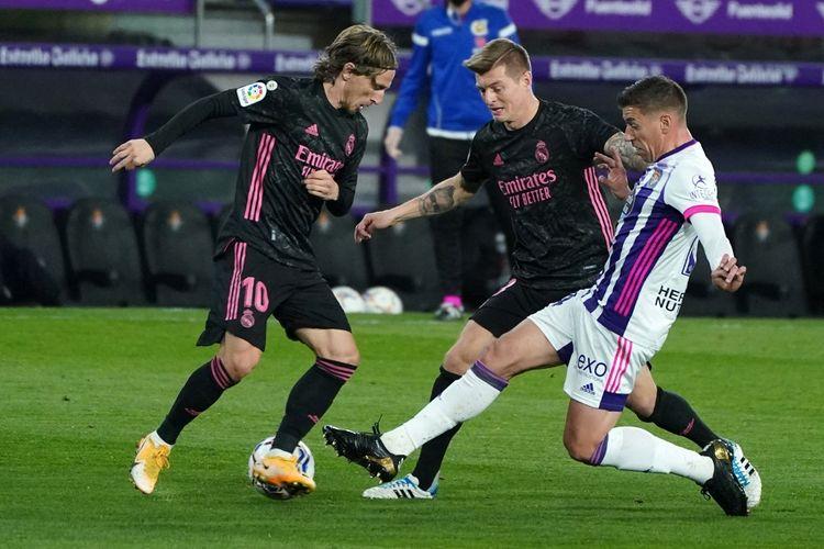 Dua gelandang Real Madrid Luka Modrid (kiri) dan Toni Kroos berebut bola dengan striker Real Valladolid Sergi Guardiola pada laga lanjutan pekan ke-24 Liga Spanyol 2020-2021 di Stadion Jose Zorilla, 20 Februari 2021.