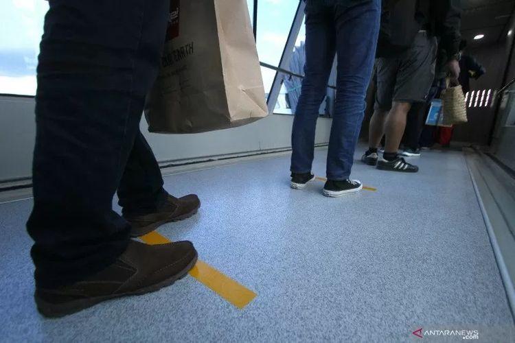 Calon penumpang berdiri mengantre di lantai yang telah diberi stiker panduan jarak saat masuk ke pesawat di Terminal Bandara Internasional Syamsudin Noor, Banjarbaru, Kalimantan Selatan, Kamis (19/3/2020) ANTARA FOTO/Bayu Pratama S/wsj. (ANTARA FOTO/BAYU PRATAMA S)