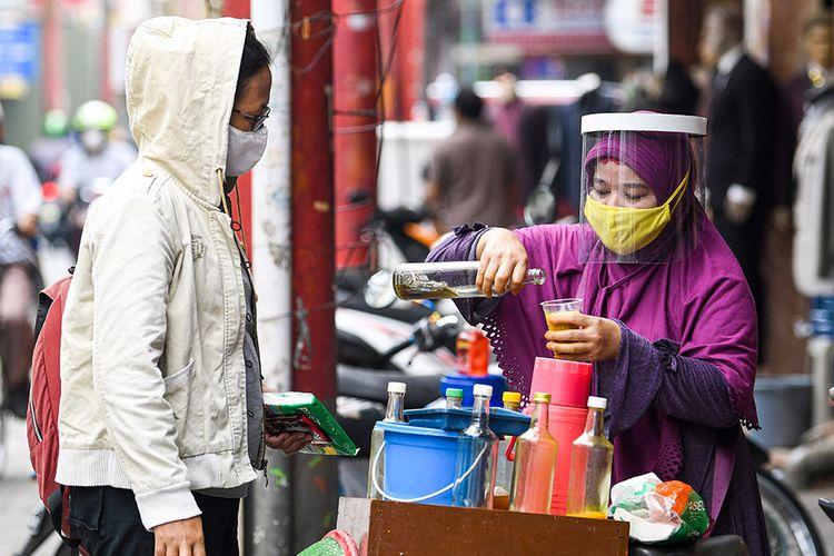 Penjual jamu keliling Tidar (kanan) dengan menggunakan masker dan pelindung wajah melayani pembeli di kawasan Pasar Baru, Jakarta, Selasa (9/6/2020). Tidar menerapkan protokol kesehatan jelang pemberlakuan protokol tatanan normal baru di Jakarta untuk tetap mencari nafkah.