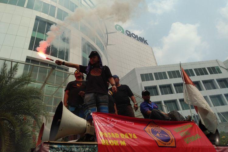 Massa aksi menghidupkan flare di depan kantor Gojek di Jalan Iskandarsyah, Melawai, Blok M, Jakarta Selatan, Senin (5/8/2019).