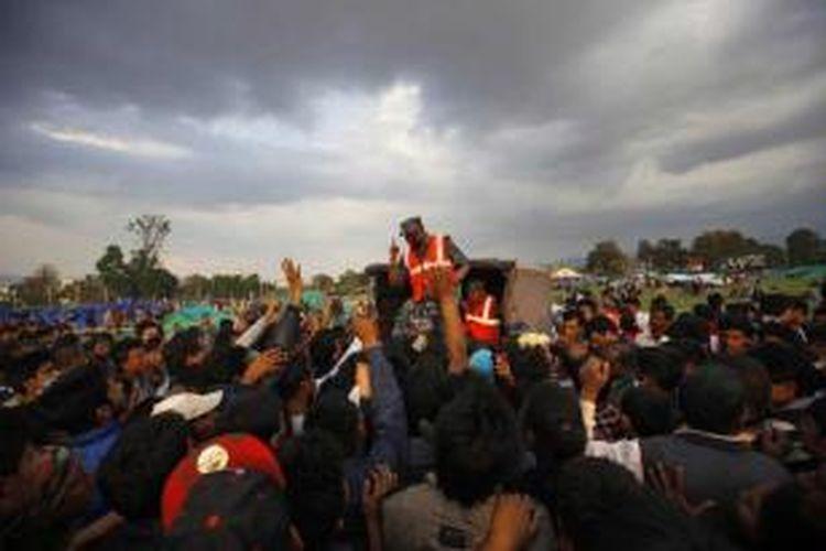 Warga korban gempa berebut pembagian tenda darurat di Kathmandu, Nepal, 26 April 2015. Gempa tektonik berkekuatan 7.9 SR mengguncang Nepal pada 25 April, mengakibatkan ribuan orang meninggal.