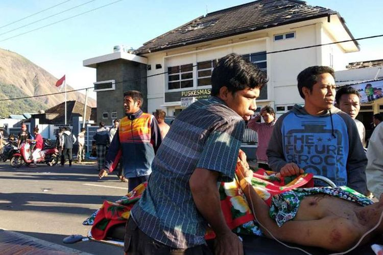 Warga korban gempa mendapatkan perawatan di luar sebuah puskesmas di Lombok, NTB, Minggu (29/7/2018). Berdasarkan informasi dari Badan Meteorologi Klimatologi dan Geofisika (BMKG) gempa pertama kali mengguncang Lombok Timur dengan kekuatan 6,4 skala Richter (SR) pada pukul 06.47 Wita.