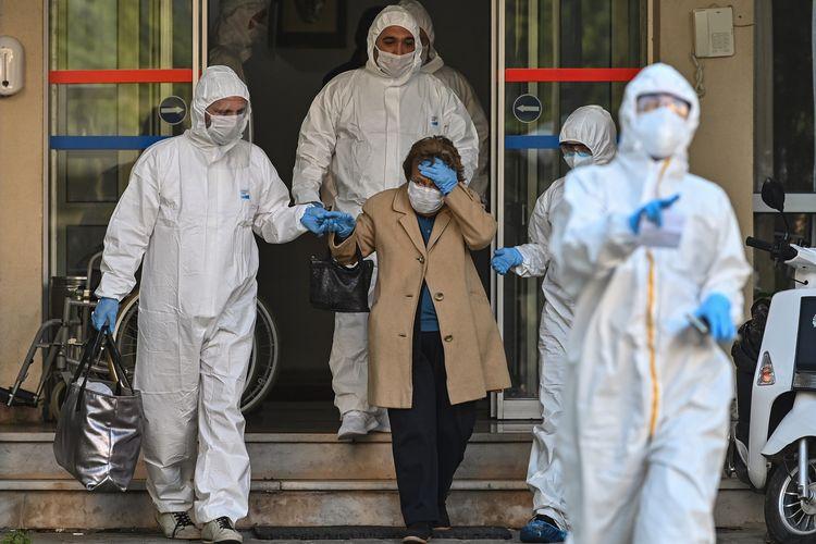 Petugas medis mengenakan pakaian pelindung mengawal perempuan yang diduga terinfeksi virus corona di Istanbul, Turki, pada 12 April 2020.