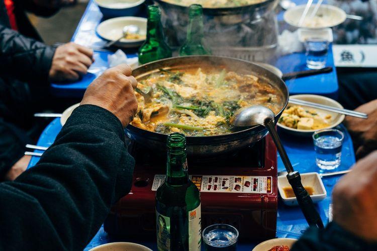Ilustrasi masakan Korea dimasak di atas kompor portabel.