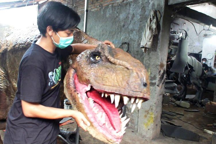 Iqbal Firmansyah Bersama Dinosaurus buatannya di Bengkel Jagad Adwork, Banguntapan, Bantul