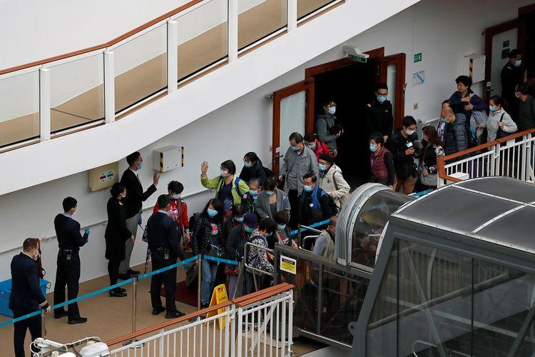 Penumpang meninggalkan kapal pesiar World Dream setelah karantina untuk mencegah penularan virus korona baru di Kai Tak Cruise Terminal di Hong Kong, China, Minggu (9/2/2020). ANTARA FOTO/REUTERS/Tyrone Siu/aww/cfo
