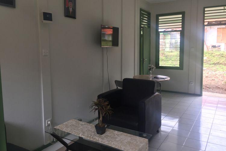 Area ruang tamu dan ruang makan yang dipisahkan dengan kursi.
