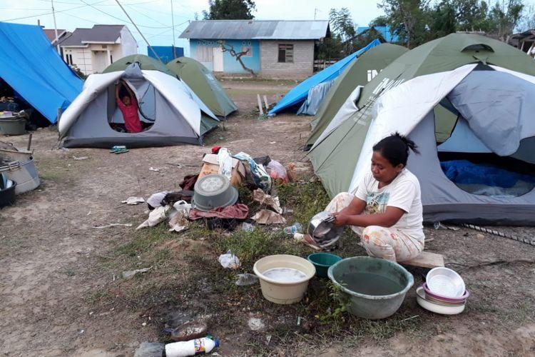 Ramna (33) warga Petobo Kota Palu sedang mencuci alat masak di pengungsian. Ia selamat dari bencana likuefaksi setelah dimuntahkan bumi.