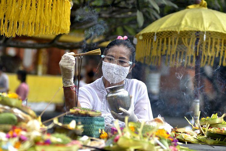 Pemuka agama Hindu memercikkan air suci saat persembahyangan Hari Raya Galungan di Pura Jagatnatha, Denpasar, Bali, Rabu (16/9/2020). Perayaan Hari Raya Galungan yang merupakan hari kemenangan kebenaran (Dharma) atas kejahatan (Adharma) tersebut diikuti umat Hindu di Pulau Dewata dengan tetap menerapkan protokol kesehatan secara ketat untuk mencegah penyebaran Pandemi COVID-19.