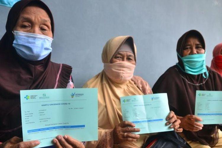 Tiga lansia di Kudus, Jawa Tengah, menunjukkan kartu vaksinasi usai menerima dosis pertama vaksin Covid-19.