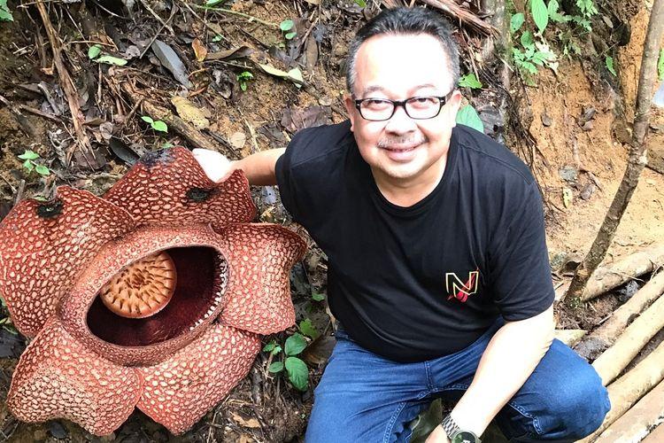 Rhenald Kasali bersama dengan bunga Rafflesia arnoldii tengah mekar di tengah hutan Bengkulu