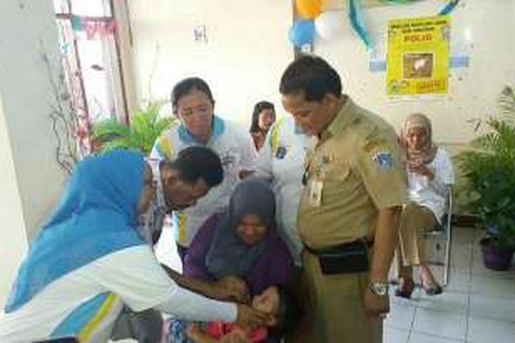 Salah seorang anak saat di imunisasi di Balai RW 02 Kelurahan Gelora, Tanah Abang, Jakarta Pusat pada Selasa (8/3/2016). Ini berkaitan dalam rangka Pekan Imunisasi Nasional (Pin) polio yang diselenggarakan pada tanggal 8-15 Maret 2016.