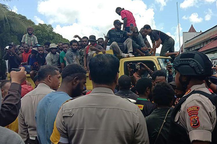 Para pengunjuk rasa menaiki truk menyusul aksi rusuh yang terjadi di sebuah universitas di Jayapura, Papua, Senin (23/9/2019). Gubernur Papua Lukas Enembe menyebut terdapat korban jiwa dan luka-luka dari kerusuhan yang masih ditelusuri penyebabnya tersebut.