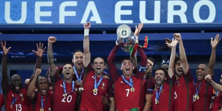 Penyerang Portugal Cristiano Ronaldo (tengah) mengangkat trofi saat merayakan kemenangan bersama timnya yang memenangi final Piala Eropa Euro 2016, Senin (11/7/2016). Portuga mengalahkan Perancis 1-0 saat final di Stade de France.