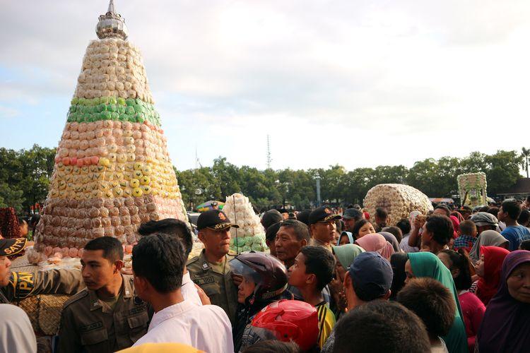 Ratusan warga mengelilingi tumpeng besar berisi ribuan butir kue apem di alun-alun Jombang Jawa Timur, Jumat (3/5/2019) petang. Menyambut Ramadhan, Pemkab Jombang setiap tahun menggelar kegiatan gerebek apem, sebagai penanda dan pengingat datangnya bulan ramadhan.