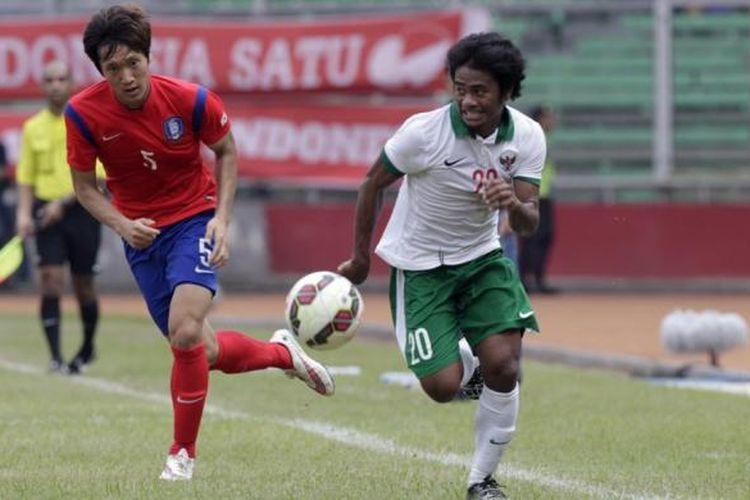 Pemain timnas Indonesia U-23 Ilham Udin berusaha melewati pemain timnas Korea Selatan U-23 Woo Jusung dalam laga kualifikasi Piala Asia U-23 Grup H di Stadion Utama Gelora Bung Karno, Senayan, Jakarta, Selasa (31/3/2014). Indonesia dikalahkan oleh Korsel dengan skor 4-0.