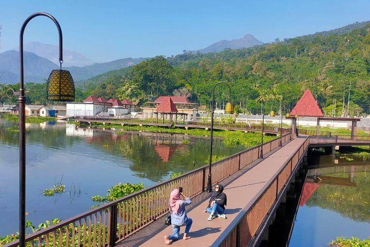 Pengunjung berfoto di jembatan panjang Bukit Cinta Rawa Pening, Ambarawa, Kabupaten Semarang, Jawa Tengah.