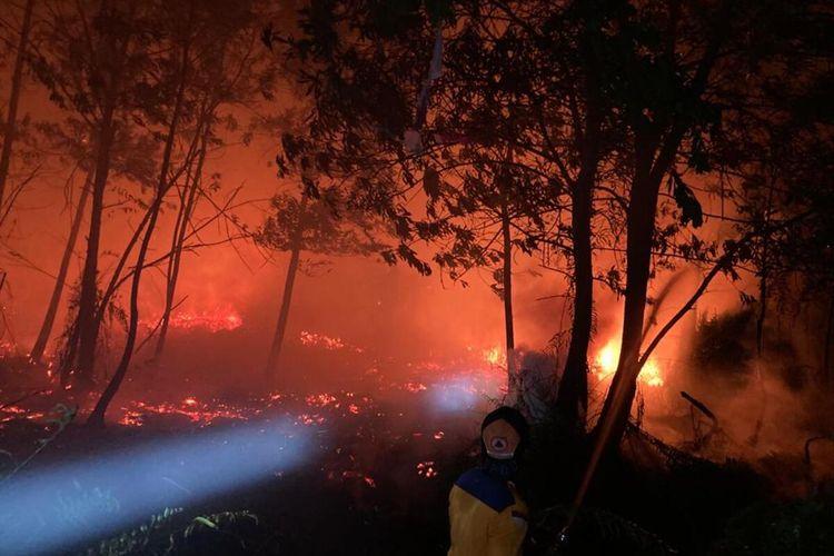 Petugas pemadam kebakaran bersama aparat terkiat berjibaku memadamkan api yang membakar sejumlah lahan di Jalan Sepakat II, Kecamatan Pontianak Tenggara, Kota Pontianak, Kalimantan Barat (Kalbar), Minggu (28/2/2021).