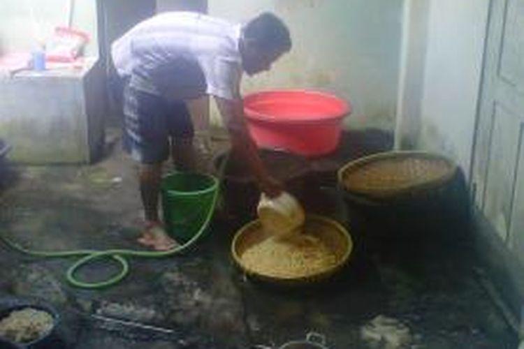 Taufiq salah satu produsen tempe saat membersihkan kedelai sebelum diolah menjadi tempe