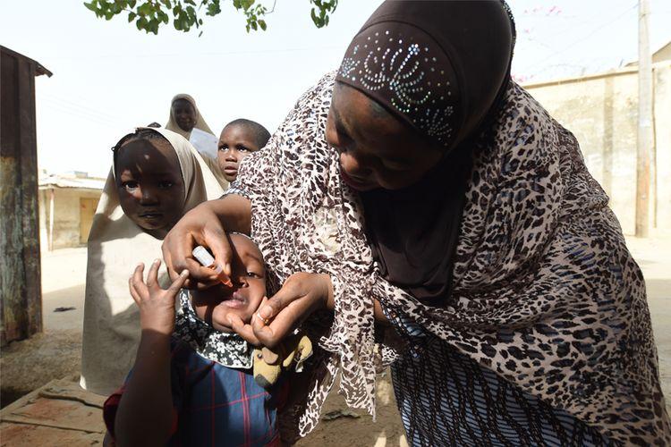 Seorang petugas kesehatan memberikan imunisasi polio di Kano, Nigeria pada 22 April 2017. PIUS UTOMI EKPEI / AFP