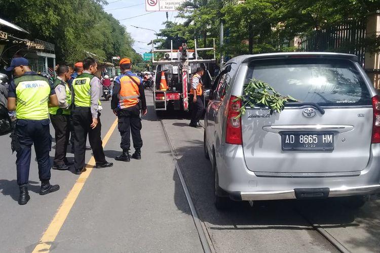 sejumlah petugas Dishub Solo melakukan penderekan terhadap mobil yang nekat parkir di atas perlintasan kereta api di Solo