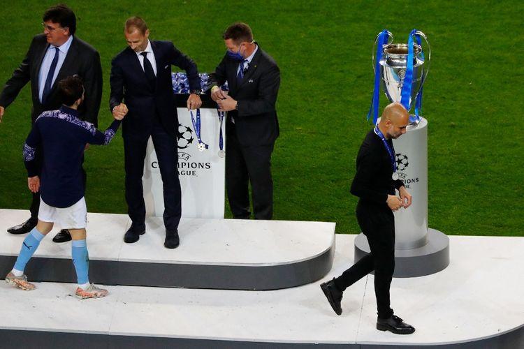 Pelatih Manchester City, Pep Guardiola, berjalan melewati trofi Liga Champions seusai kekalahan melawan Chelsea di laga final di Stadion Dragao, Porto, pada Minggu (30/5/2021) dini hari WIB.