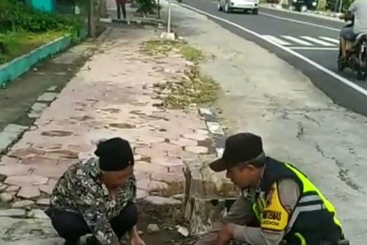 Aipda Adi Novianto membantu seorang ibu memungut beras yang jatuh.
