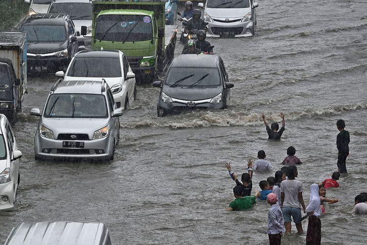 Sejumlah pengendara kendaraan bermotor melintasi Jalan Gunung Sahari yang mengalami banjir di Pademangan, Jakarta, Jumat (24/1/2020). Hujan yang mengguyur sejak Jumat pagi hingga siang hari tersebut memicu banjir setinggi 30-50 centimeter di jalan raya itu sehingga menyebabkan lalu lintas kendaraan bermotor dan roda perekonomian warga setempat tersendat.