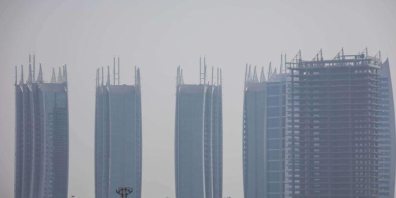 Pemandangan laut dengan latar belakang gedung bertingkat yang diselimuti asap polusi di Jakarta Utara, Rabu (31/7/2019). Berdasarkan data situs penyedia peta polusi daring harian kota-kota besar di dunia AirVisual, menempatkan Jakarta pada urutan pertama kota terpolusi sedunia pada Senin (29/7) pagi dengan kualitas udara mencapai 183 atau dalam kategori tidak sehat.