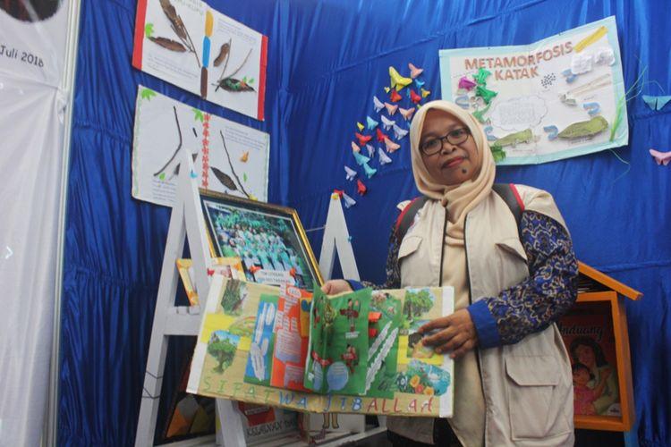 Dharmawati, Kepala Sekolah SD 037 Nunukan, menunjukkan buku dari alam yang dibuat sendiri oleh guru dan siswa dalam pameran di seminar nasional literasi kelas awal yang diselenggarakan oleh Inovasi di Universitas Borneo, Tarakan, Kaltara, Kamis (19/7/2018).