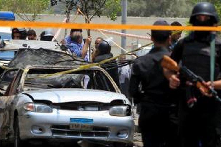 Polisi mengamankan lokasi serangan bom mobil terhadap konvoi Jaksa Penuntut Umum Mesir, Hisham Barakat, di dekat rumahnya di distrik Heliopolis di Kairo pada 29 Juni 2015.