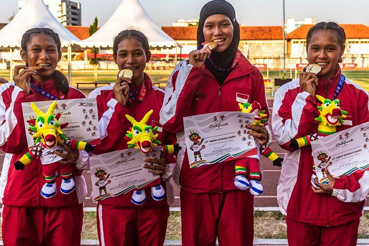Tim pelari Indonesia Daniela Elim (kanan), Diva Aprilian (kedua kanan), Erna Nuryanti (kedua kiri) dan Raden Roselin (kiri) berfoto dengan medali emas usai penyerahan medali final Lari Estafet 4x100 meter Putri Atletik ASEAN Schools Games ke-11 Tahun 2019 di GOR Tri Lomba Juang, Semarang, Jawa Tengah, Senin (22/7/2019). Tim pelari putri Indonesia berhasil meraih medali emas dengan catatan waktu 46.83 detik disusul tim pelari Thailand dengan medali perak (47.20 detik) dan tim pelari Malaysia dengan medali perunggu (47.73 detik).