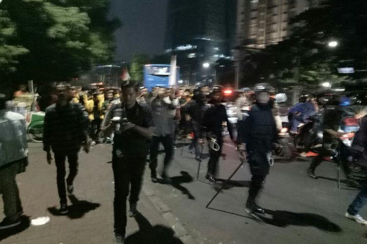 Sebagian mahasiswa mendapatkan pengawalan petugas kepolisian dan TNI saat membubarkan diri usai menggelar aksi unjuk rasa di gedung DPR Selasa, (1/10/2019).