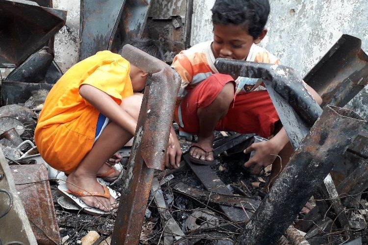 Braja (12) dan Ardan (6) mencari uang koin diantara bangkai bangunan bekas kebakaran di Jalam Perumahan Taman Kota, RT 16 RW 05, Kembangan Utara, Kembangan, Jakarta Barat pada Minggu (1/4/2018).