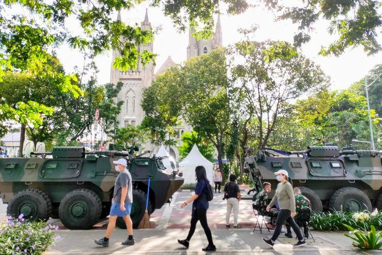 Sejumlah warga berjalan di depan Gereja Katedral, Jakarta Pusat yang dijega ketat personel TNI-Polri, Jumat (2/4/2021).