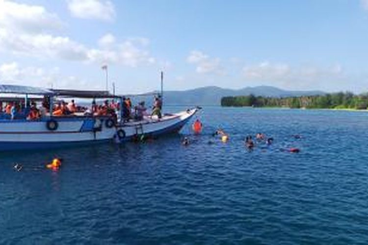 Para wisatawan sedang menikmati Laut Karimunjawa dengan melakukan snorkeling saat mengikuti paket wisata