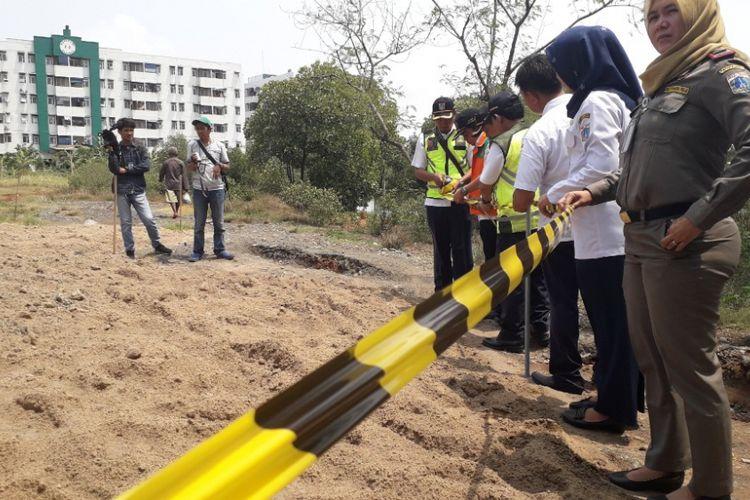 Petugas Dinas LH memasang garis pembatas di area temuan gundukan yang diduga limbah B3 di kawasan Marunda, Jakarta Utara, Rabu (9/1/2019).