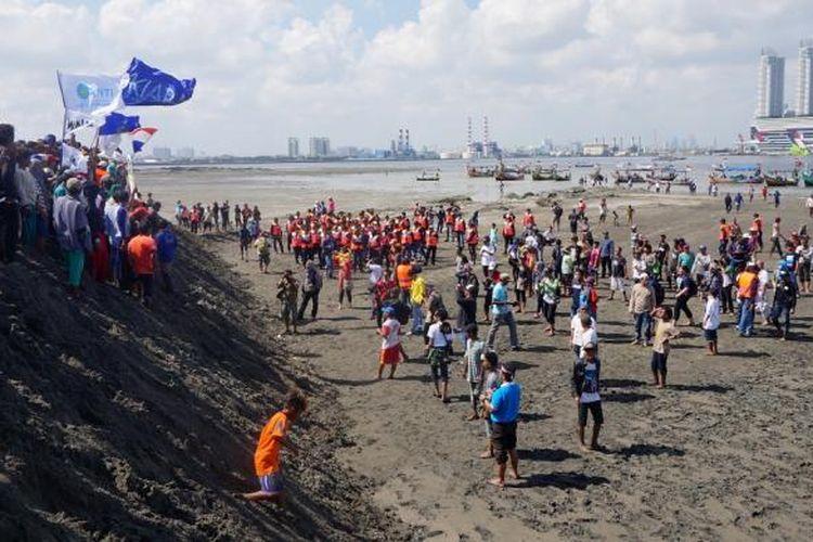 Warga menjejakkan kaki pertama kali di Pulau G, saat melakukan aksi penyegelan pulau, Minggu (17/4/2016). Aksi yang diikuti ratusan warga pesisir Jakarta ini merupakan bentuk penolakan reklamasi Teluk Jakarta yang tengah berlangsung.