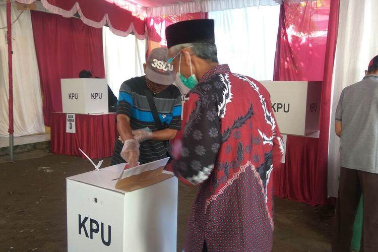 Dengan memakai masker dan sarung tangan plastik, pemilih menyalurkan hak pilihnya di TPS 02, Desa/Kecamatan Pangandaran, Kabupaten Pangandaran, Rabu (9/12/2020).