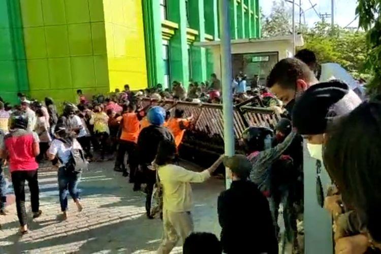 Warga merobohkan pagar Gedung Jurusan Farmasi, Poltekes Kemenkes Kupang, saat antre untuk mendapatkan vaksin Covid-19, Rabu (14/6/2021)