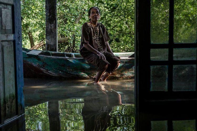 Seorang warga Demak, Pasijah, duduk di perahu yang bertengger di teras rumahnya yang tergenang air laut.