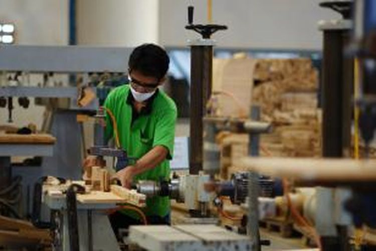 Ilustrasi: Salah seorang pekerja pabrik mebel tengah melubangi kayu jati dengan menggunakan horizontal bor.