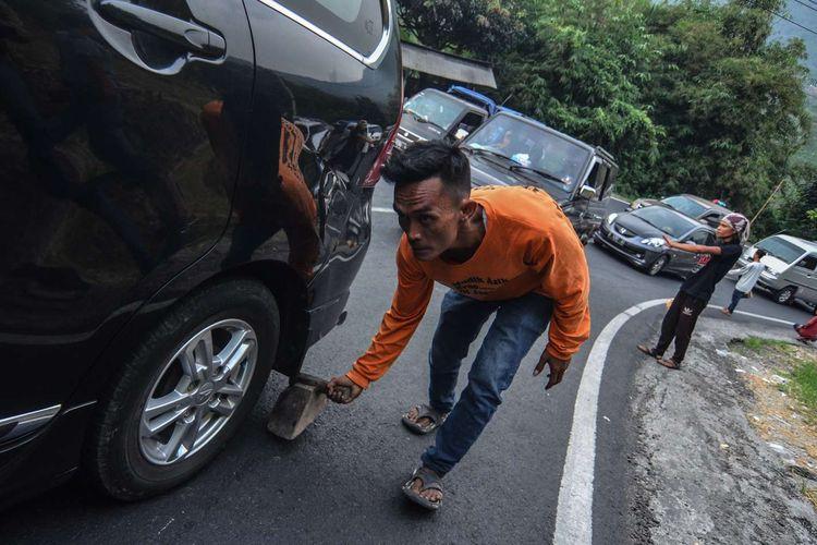 Seorang tukang ganjal mengganjal ban mobil pemudik yang tidak kuat melintas pada arus balik H+2 Lebaran di Tanjakan Gentong, Kabupaten Tasikmalaya, Jawa Barat, Jumat (7/6/2019).