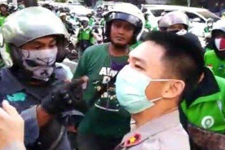 Pengemudi ojek online meluapkan kekesalan kepada polisi karena membubarkan pembagian nasi kotak.
