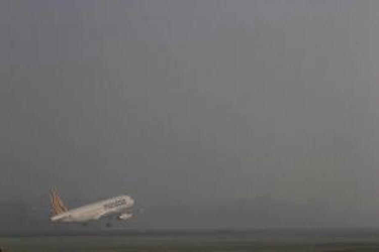 Pesawat komersil terbang sebelum Bandara Sultan Syarif Kasim II Pekanbaru lumpuh selama tiga jam akibat pekatnya kabut asap, Kamis (20/6/2013). Kabut asap akibat kebakaran lahan dan hutan yang melanda wilayah Riau menyebabkan jarak pandang hanya mencapai 750 meter sehingga sejumlah penerbangan terpaksa ditunda dan dialihkan. TRIBUN PEKANBARU/MELVINAS PRIANANDA