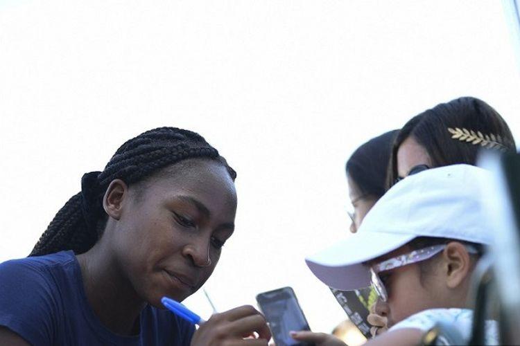 Petenis remaja AS berusia 15 tahun, Cori Gauff (kiri), memberi tanda tangan kepada penggemar setelah sesi latihan di The All England Tennis Club di Wimbledon, London, Inggris, pada 4 Juli 2019, pada hari keempat turnamen tenis Wimbledon 2019.