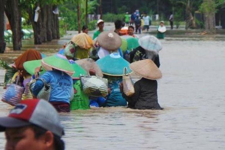 Sejumlah petani bawang menembus banjir akibat meluapkan Sungai Pemali, Kabupaten Brebes, Jawa Tengah, Kamis (16/2/2017).