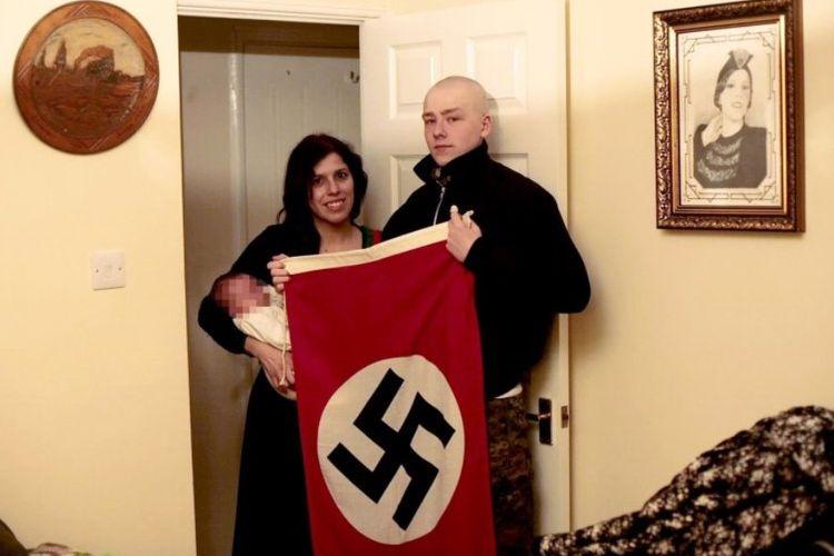 Pasangan Adam Thomas (22) dan kekasihnya Claudia Patatas (38) berfoto sambil membawa bendera Nazi dengan putra mereka yang diberi nama Adolf. Keduanya dituduh sebagai anggota kelompok sayap kanan terlarang Aksi Nasional.